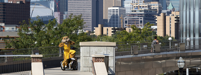 Goldy Gopher on campus with a view of Minneapolis in the background